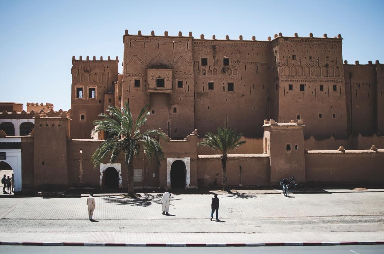 Een oud gebouw midden in Marokko waar mensen naar staan te kijken.