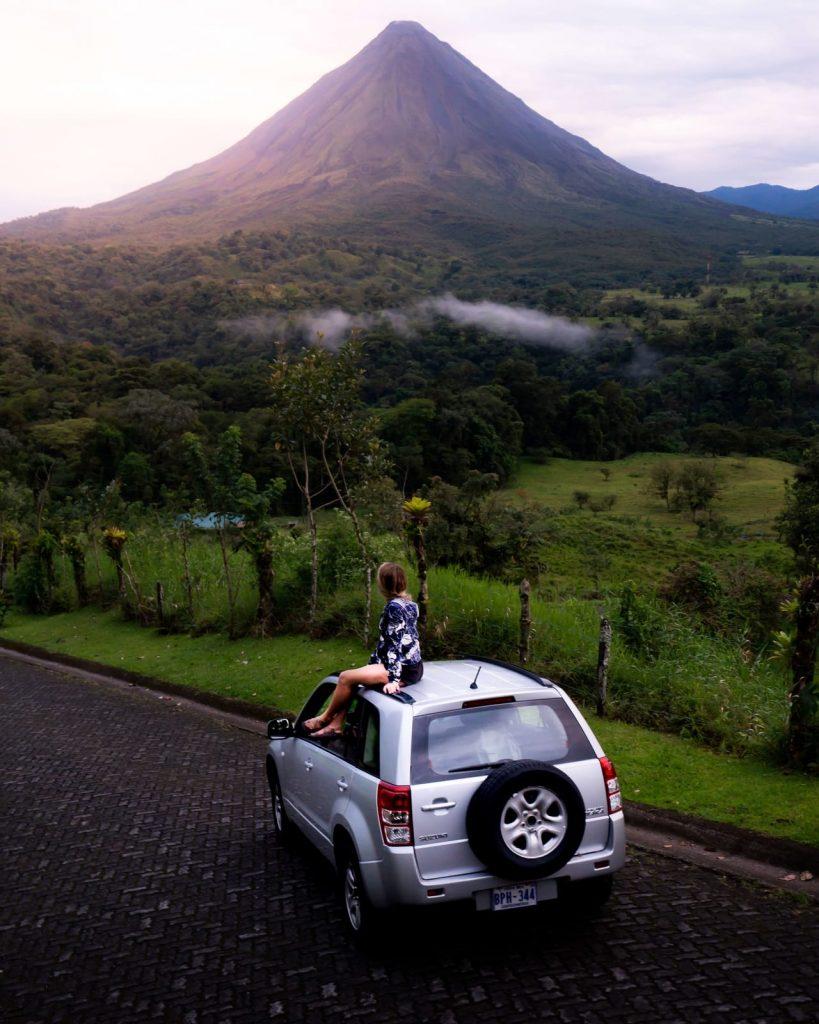 Een vrouw op een auto kijkend naar de Arenal vulcaan in Costa Rica