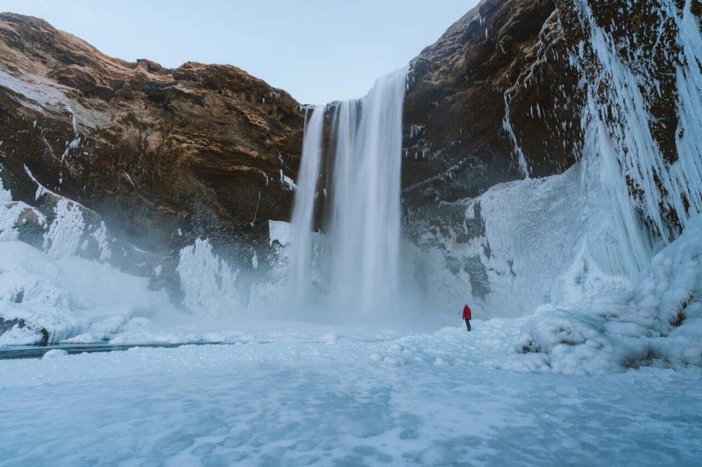 Waterval in IJsland met een persoon die er van dichtbij naar kijkt.