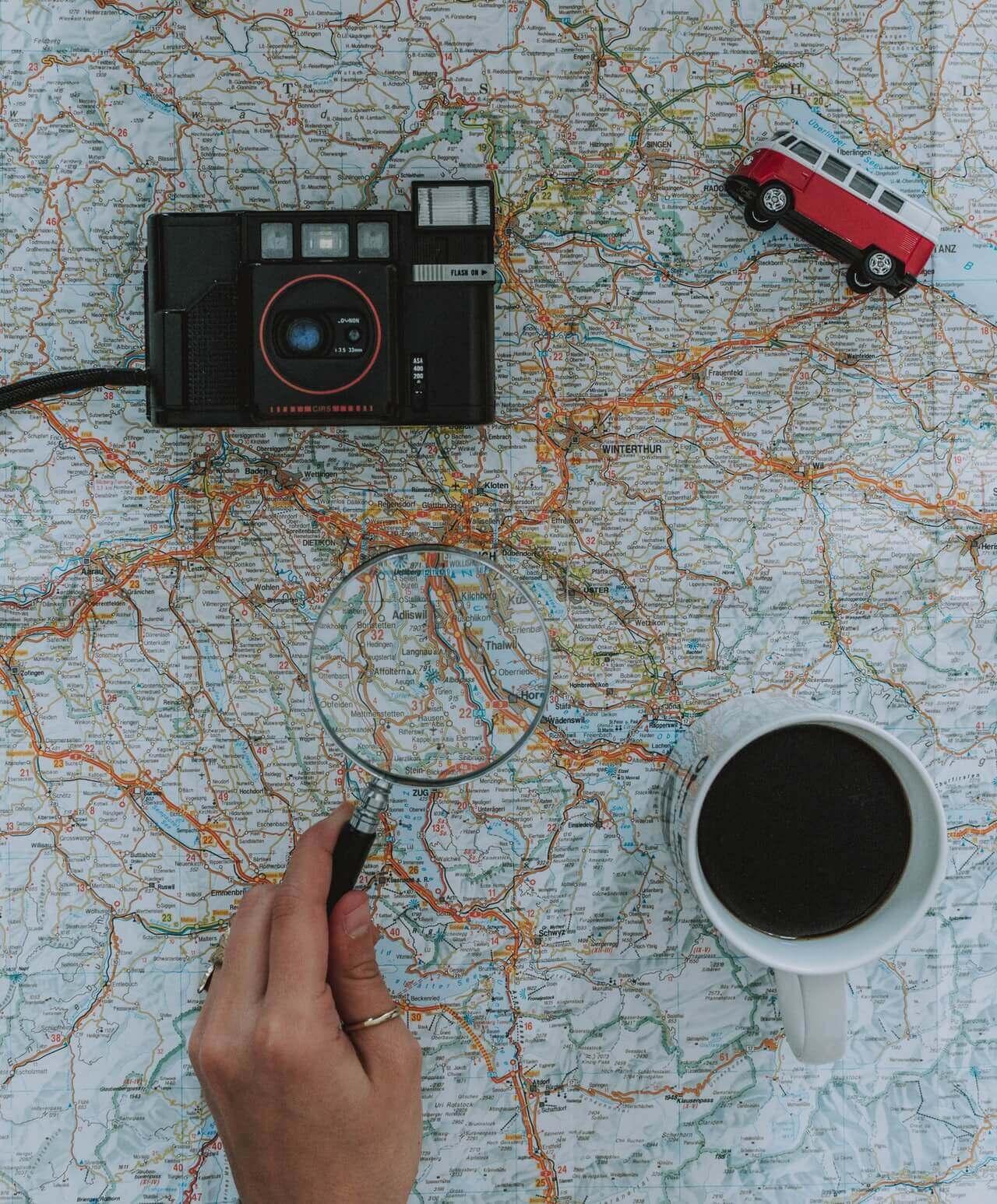 Wereldkaart met daarop een fototoestel, een speelgoed busje en een kopje koffie.