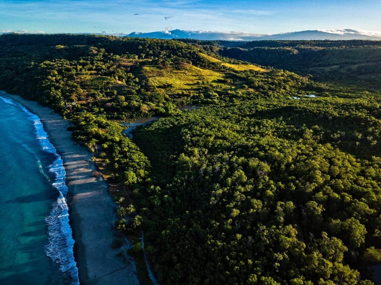 Luchtfoto van een strand in Costa Rica met aangrenzend de natuur met bomen.