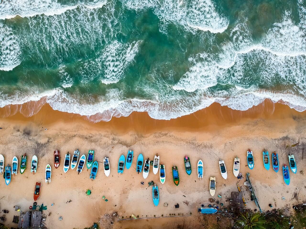 Bovenaanzicht van een strand in Sri Lanka met allemaal gekleurde boten.