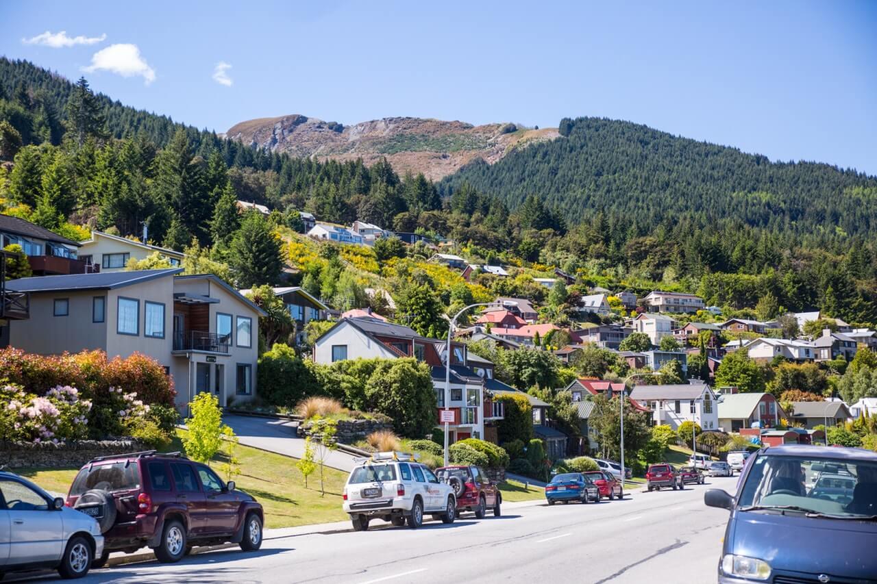 Straat in een stad van Nieuw-Zeeland met auto's en huizen.