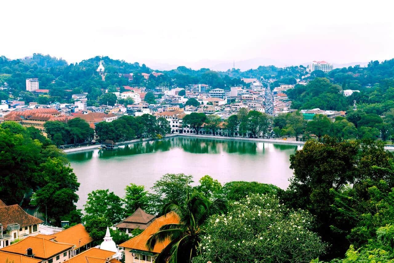 Een luchtfoto van een stad met allemaal huizen en in het midden een meer in Sri Lanka.