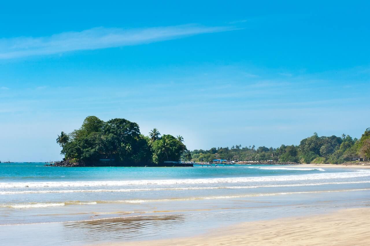 Het strand van Sri Lanka met in de verte een eilandje met veel bomen.