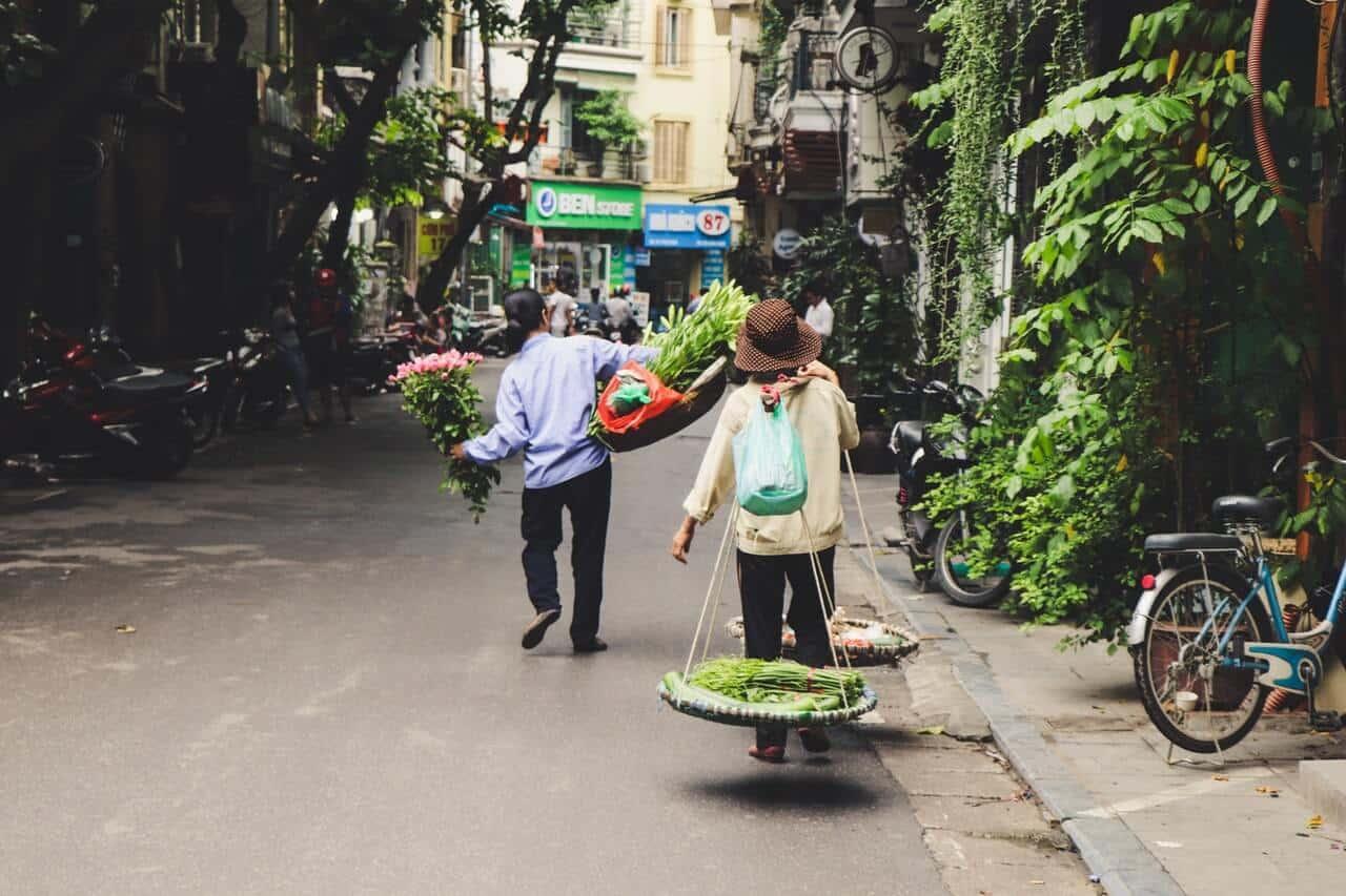 Straat in Vietnam waar een man en een vrouw lopen met hun handelswaar voor op de markt.