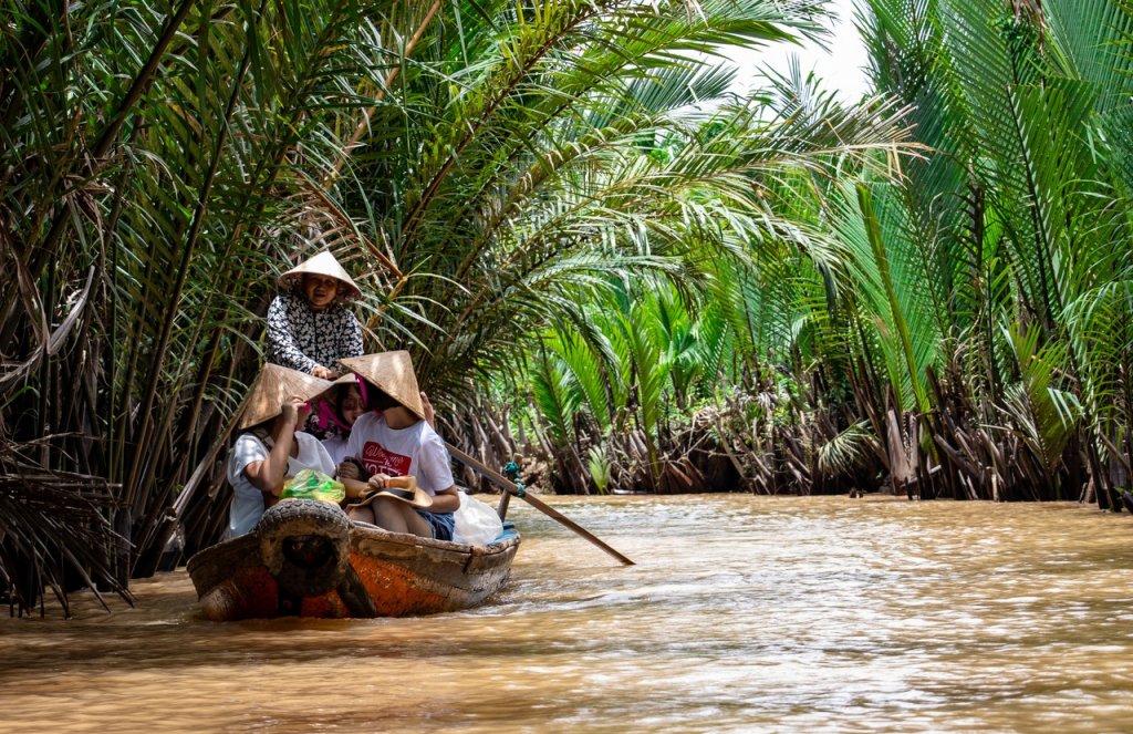 Een bootje op de rivier in de jungle met hierop vier Vietnamese vrouwen.