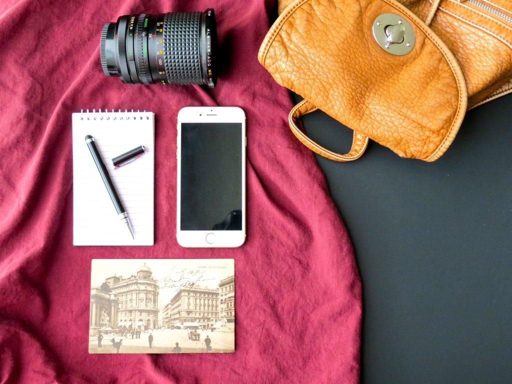 Spullen in een backpack, namelijk: smartphone, pen, cameralens en foto.