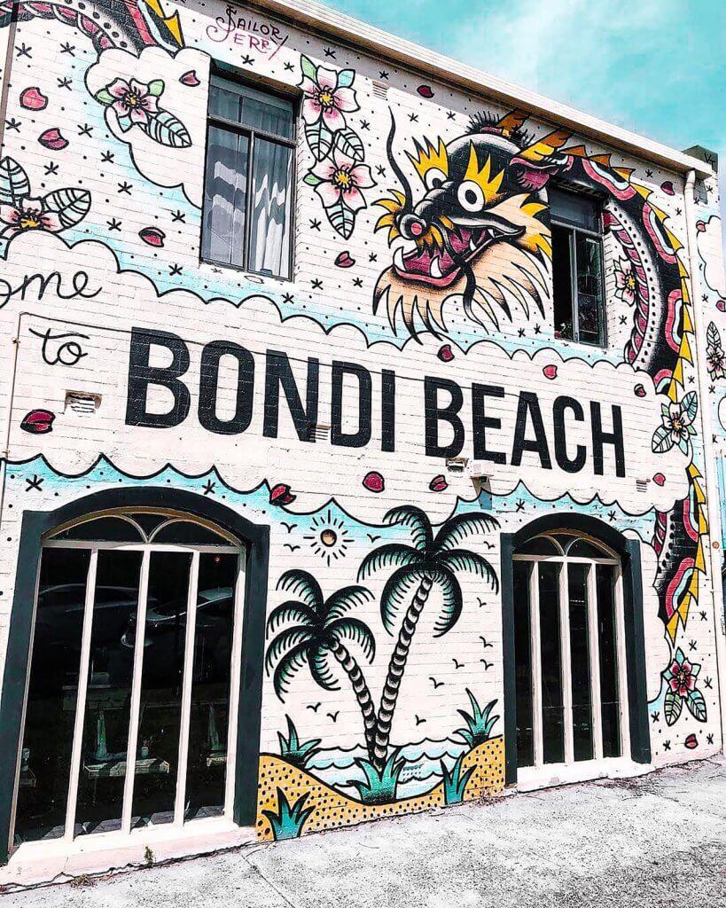"""Een muurschildering van een draak en met de tekst """"Bondi Beach"""" in Australië"""